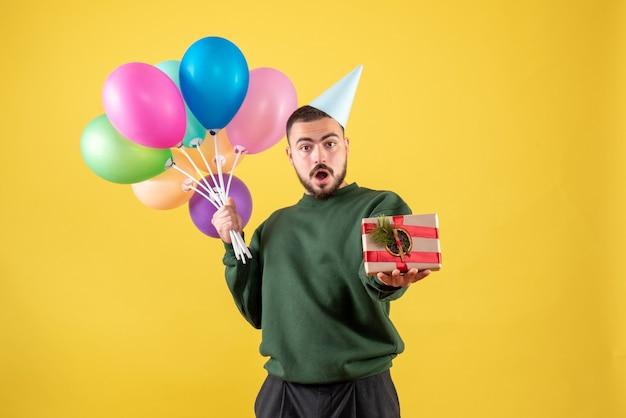 Vorderansicht junger mann, der bunte ballons hält und auf gelbem hintergrund präsentiert