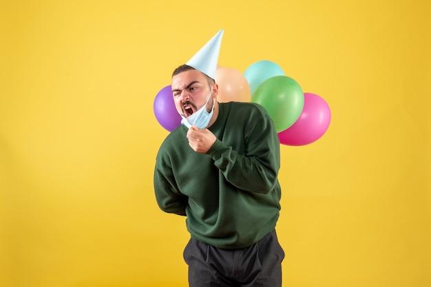 Vorderansicht junger mann, der bunte luftballons auf gelbem schreibtisch hält