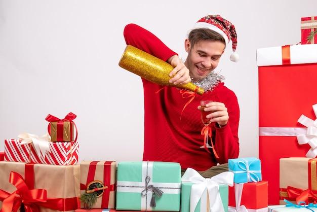 Vorderansicht junger mann, der champagner gießt, der um weihnachtsgeschenke sitzt