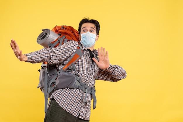 Vorderansicht junger mann, der das wandern in der maske auf gelb vorbereitet
