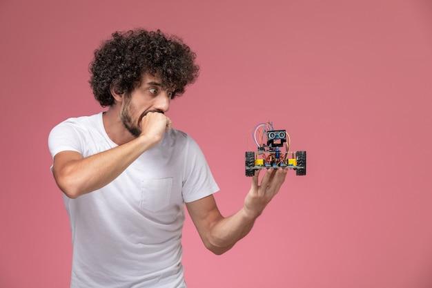 Vorderansicht junger mann, der durch seinen elektronischen roboter erschreckt wird