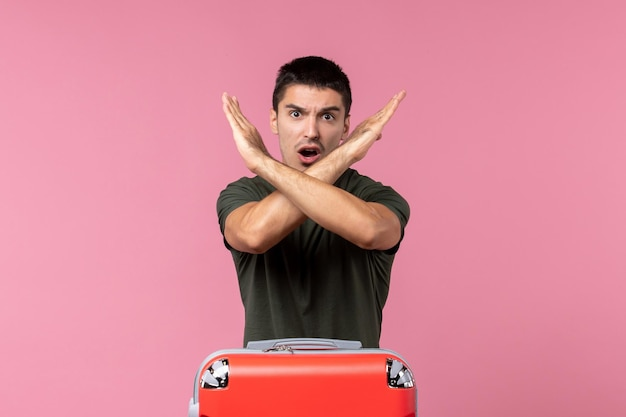 Vorderansicht junger mann, der ein verbotszeichen auf dem rosafarbenen raum zeigt