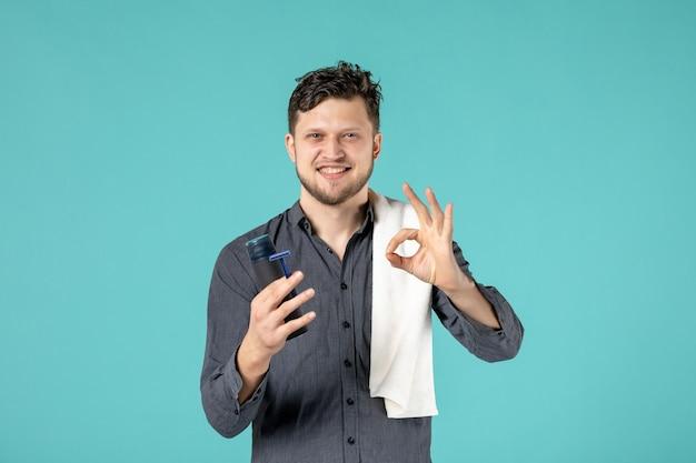 Vorderansicht junger mann, der einen rasierer auf blauem hintergrund hält