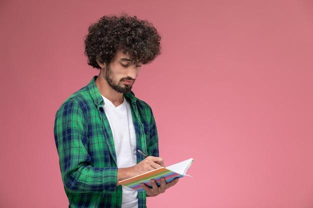 Vorderansicht junger mann, der einige notizen auf rosa hintergrund macht