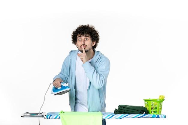 Vorderansicht junger mann, der eisen hält und jemanden auffordert, auf weißem hintergrund zu schweigen eisenfarbe mann wäsche kleidung hausarbeit reinigung emotion