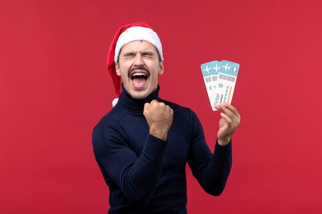 Vorderansicht junger mann, der emotional tickets auf rotem hintergrund hält