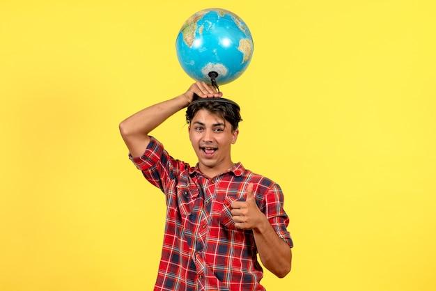 Vorderansicht junger mann, der erdkugel auf männlichem modellfarbe des gelben hintergrunds hält
