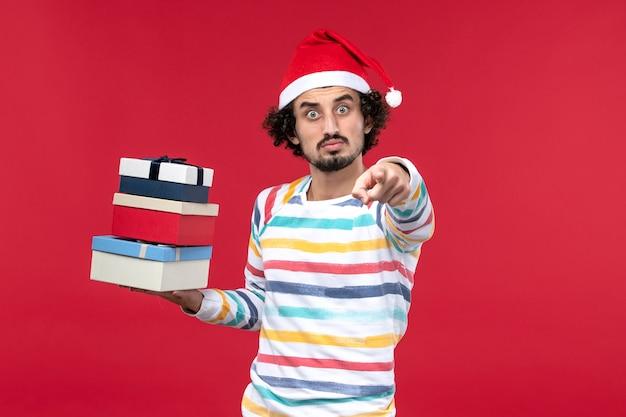 Vorderansicht junger mann, der feiertagsgeschenke auf roten wandfeiertags-neujahrsgefühlen hält