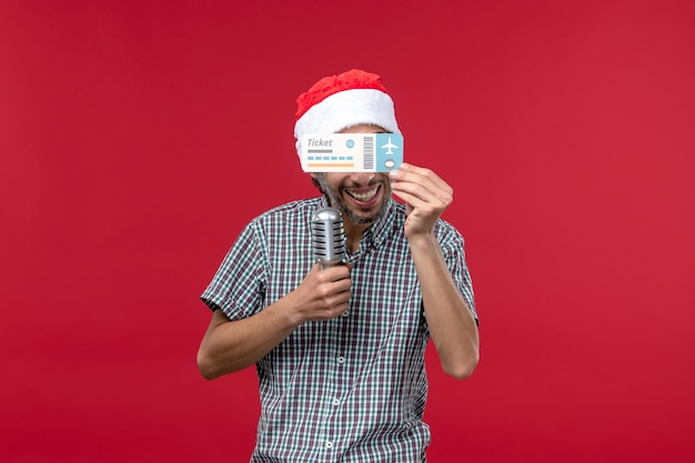 Vorderansicht junger mann, der flugschein und mikrofon auf rotem hintergrund hält