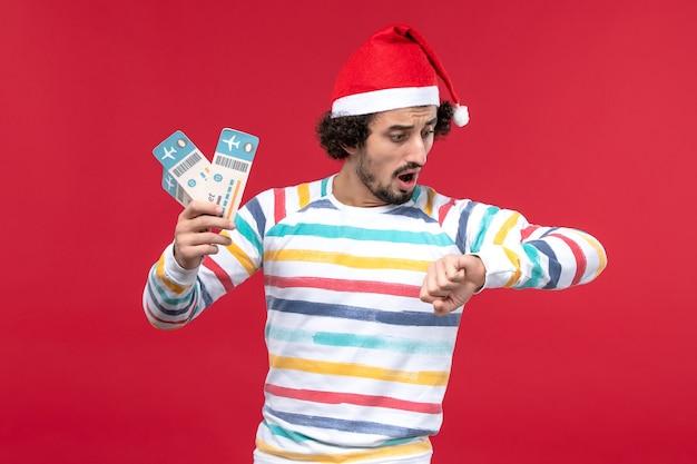 Vorderansicht junger mann, der flugtickets auf rotem hintergrund flugzeugfeiertag neujahr rot hält