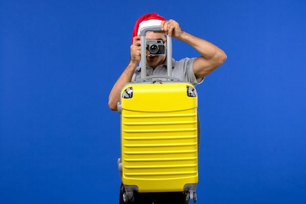 Vorderansicht junger mann, der foto mit kamera auf blauem wandflugferienflugzeug nimmt