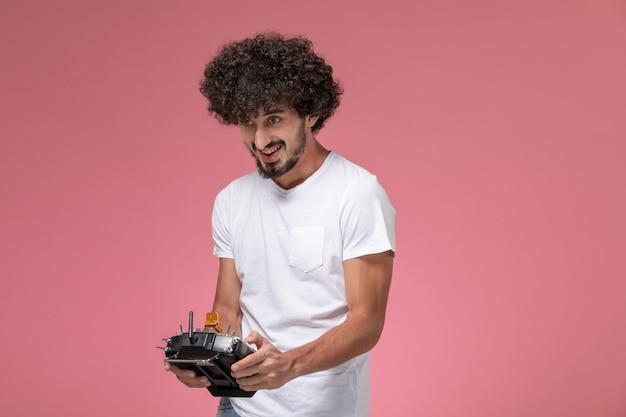Vorderansicht junger mann, der funksteuerung für elektronischen roboter verwendet
