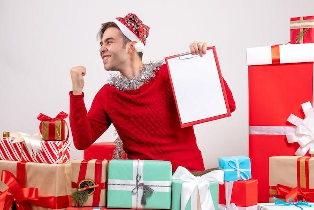 Vorderansicht junger mann, der gewinnende geste zeigt, die um weihnachtsgeschenke sitzt