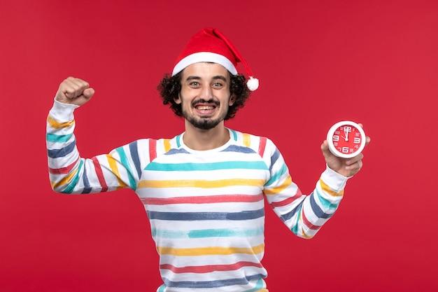 Vorderansicht junger mann, der glücklich uhren auf rotem boden neujahrsfeiertag roter mann hält