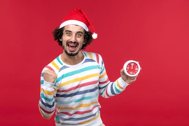 Vorderansicht junger mann, der glücklich uhren auf roter wand neujahrsfeiertag roter mann hält