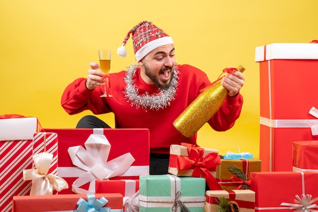 Vorderansicht junger mann, der herum geschenke mit champagner auf gelbem hintergrund sitzt