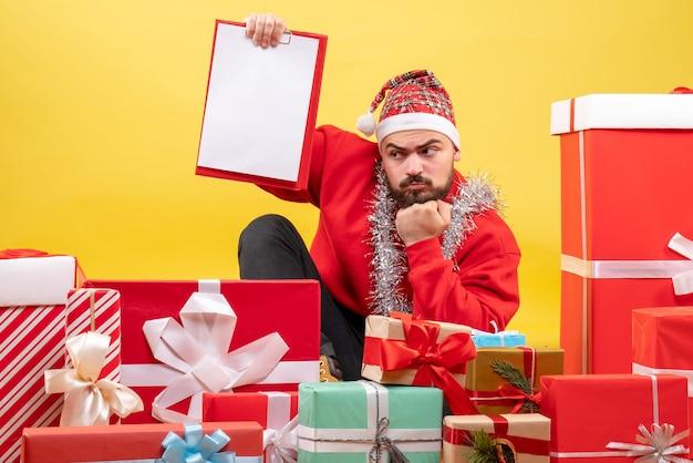 Vorderansicht junger mann, der herum geschenke mit notiz auf gelbem schreibtisch sitzt