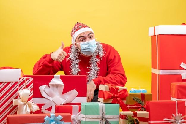 Vorderansicht junger mann, der herum sitzt, präsentiert in steriler maske auf gelbem hintergrundfarbe pandemievirus covid-xmas