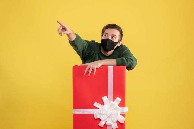 Vorderansicht junger mann, der hinter großer geschenkbox auf gelb steht