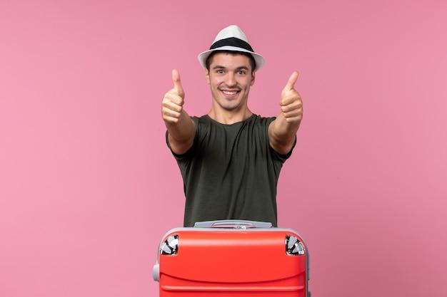 Vorderansicht junger mann, der im urlaub mit großer tasche auf rosafarbenem raum lächelt