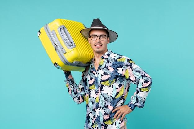 Vorderansicht junger mann, der in den urlaub geht und seine gelbe tasche auf dem blauen raum hält