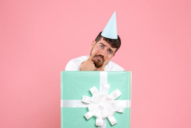 Vorderansicht junger mann, der innerhalb der gegenwärtigen box auf dem rosa farbemotionsweihnachtsfotojahrmensch steht