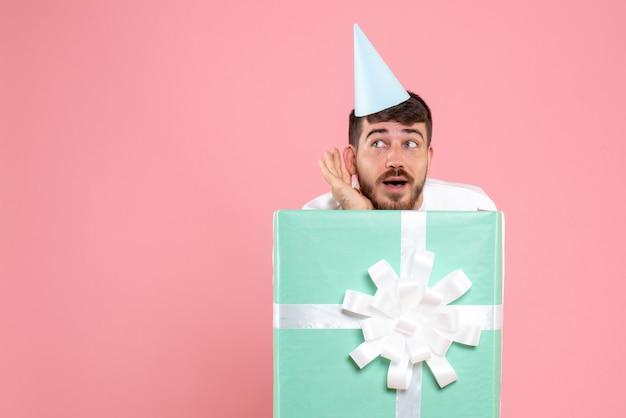 Vorderansicht junger mann, der innerhalb der gegenwärtigen box auf hellrosa farbe menschliches gefühls-weihnachtsfoto-pyjama-party steht