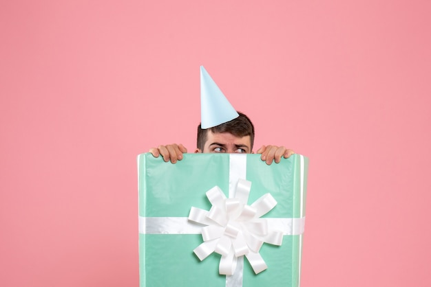 Vorderansicht junger mann, der innerhalb der gegenwärtigen box auf hellrosa farbe weihnachten neujahrsfoto emotion mensch steht