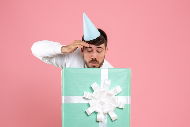 Vorderansicht junger mann, der innerhalb der gegenwärtigen box auf hellrosa fotofarbe der menschlichen emotion-weihnachtspyjama-partei steht