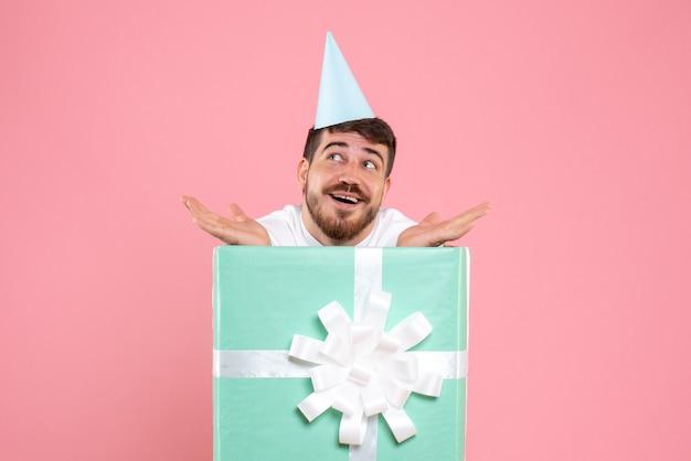 Vorderansicht junger mann, der innerhalb der gegenwärtigen box auf rosa farbe weihnachten neujahrsfoto emotion mensch steht