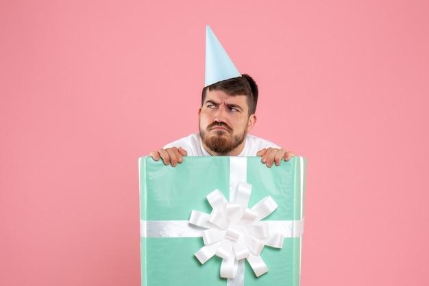 Vorderansicht junger mann, der innerhalb der gegenwärtigen box auf rosa farbe weihnachten neujahrsfoto emotionen menschlich steht