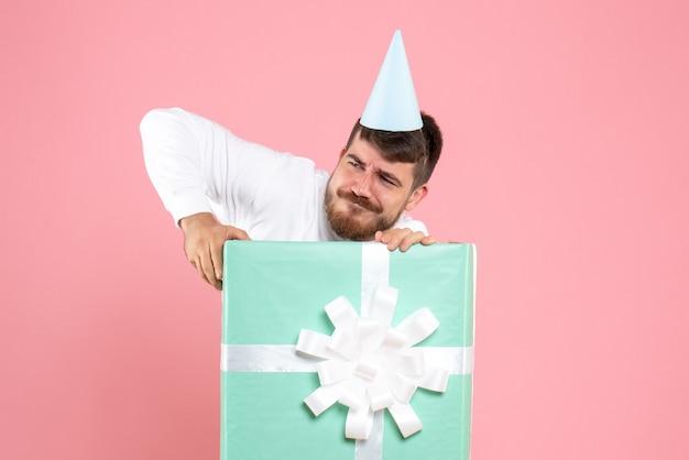 Vorderansicht junger mann, der innerhalb der gegenwärtigen box auf rosa farbemotionsweihnachtsfoto-neujahrsfoto-pyjama-party steht