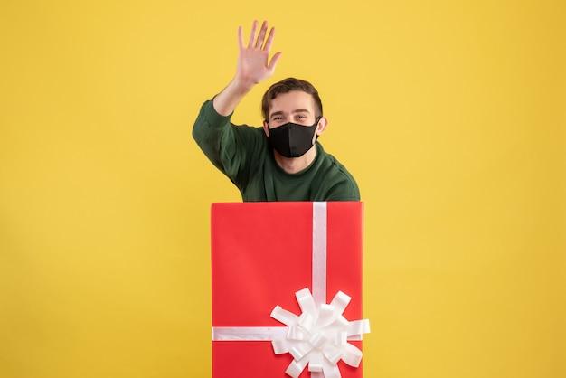 Vorderansicht junger mann, der jemanden hinter großer geschenkbox auf gelb begrüßt
