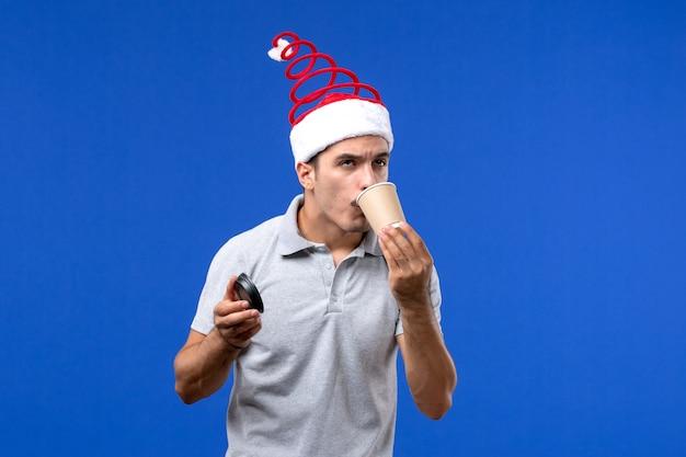 Vorderansicht junger mann, der kaffee auf der männlichen neujahrsfeiertagsemotion der blauen wand trinkt