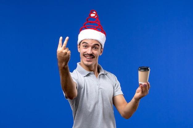 Vorderansicht junger mann, der kaffeetasse an den männlichen feiertagsemotionen der blauen wand des neuen jahres hält