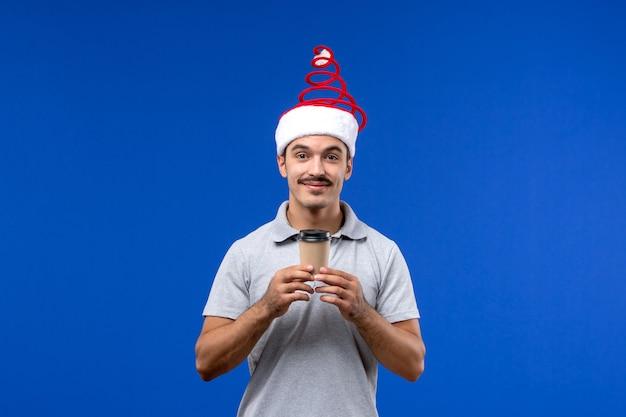 Vorderansicht junger mann, der kaffeetasse an der blauen wand neujahrsfeiertag hält