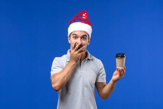 Vorderansicht junger mann, der kaffeetasse auf blauem schreibtisch neujahrsfeiertag hält