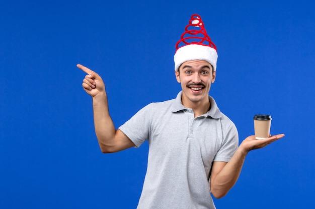 Vorderansicht junger mann, der kaffeetasse auf blauem wandgefühl neujahrsmann hält