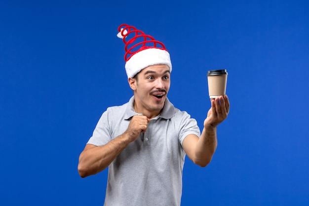Vorderansicht junger mann, der kaffeetasse auf männlicher feiertagsemotion der blauen wand des neuen jahres hält