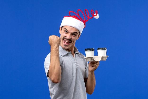 Vorderansicht junger mann, der kaffeetassen auf blauem wandgefühle kaffeeblauer mensch hält