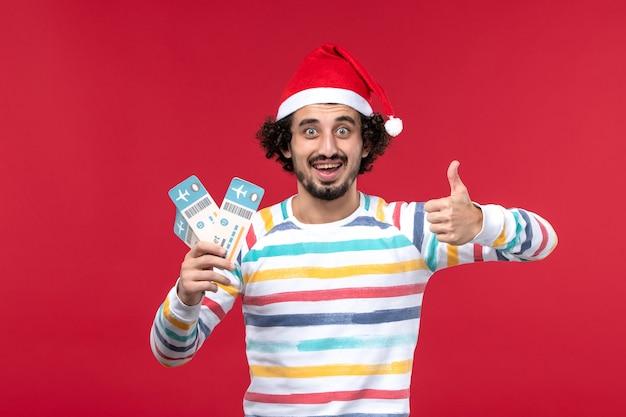 Vorderansicht junger mann, der karten auf rotem wand männlichem feiertags-neujahrsrot hält