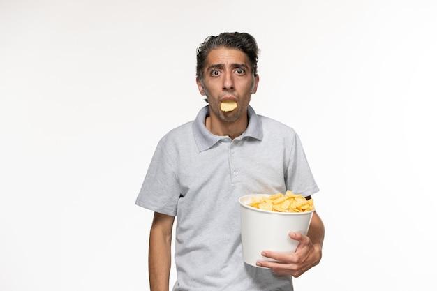 Vorderansicht junger mann, der kartoffelchips hält und film auf weißer oberfläche sieht