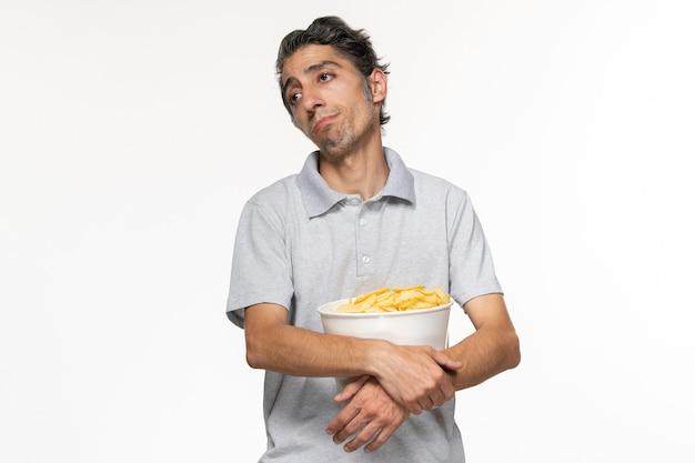 Vorderansicht junger mann, der kartoffelchips isst, während er auf filme wartet, endet auf weißer oberfläche