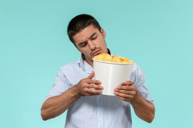 Vorderansicht junger mann, der kartoffelspitzen auf einem einsamen entfernten männlichen filmkino des blauen schreibtisches hält