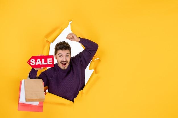 Vorderansicht junger mann, der kleine pakete und verkaufsschreiben auf gelbem hintergrund hält geschenk weihnachtsfeiertagseinkaufsfarbe