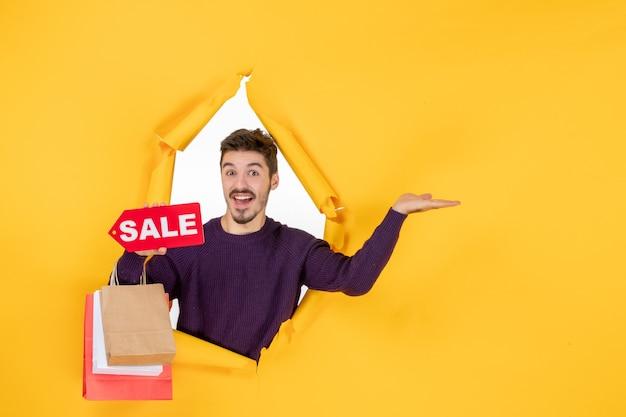 Vorderansicht junger mann, der kleine pakete und verkaufsschreiben auf gelbem hintergrund hält, präsentiert einkaufsgeschenk weihnachtsfoto