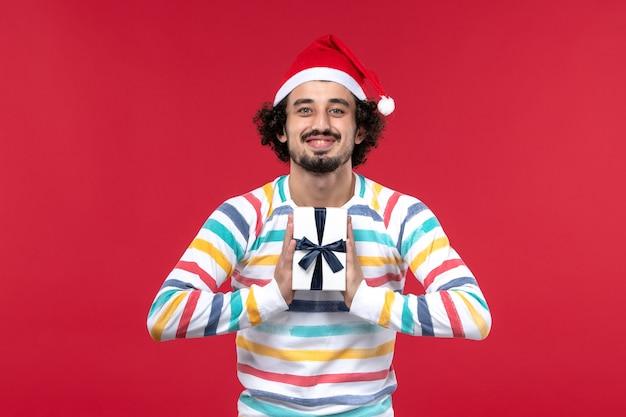 Vorderansicht junger mann, der kleines geschenk auf rotem hintergrund rote feiertage neujahrsgefühl hält
