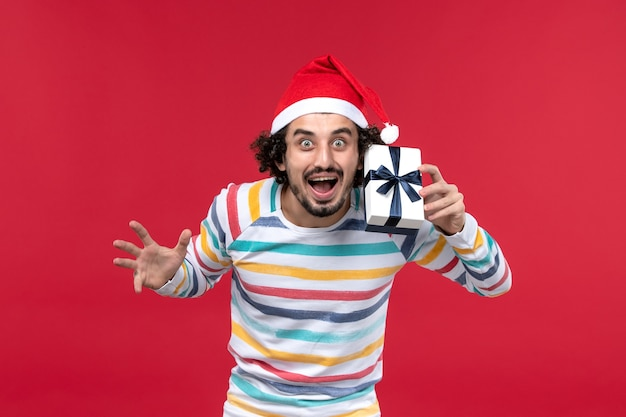 Vorderansicht junger mann, der kleines geschenk auf rotem hintergrund rotem gefühlsfeiertag neues jahr hält