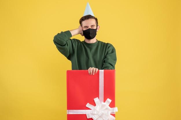Vorderansicht junger mann, der kopf steht hinter großer geschenkbox auf gelb