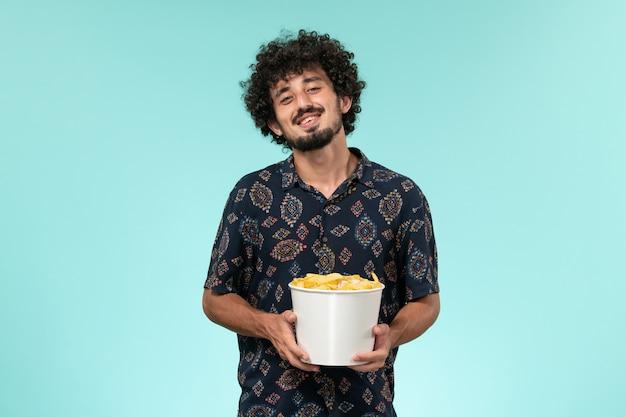 Vorderansicht junger mann, der korb mit cips auf dem ferngesteuerten kinofilm des blauen hintergrunds hält
